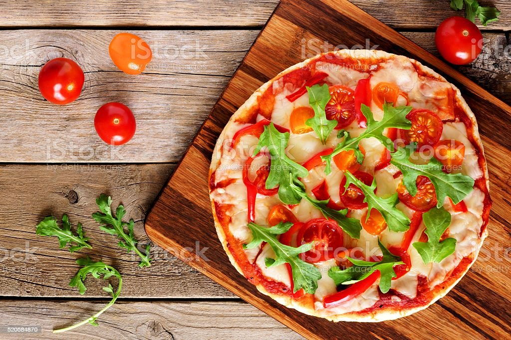 Homemade pizza with arugula and tomatoes over wood stock photo