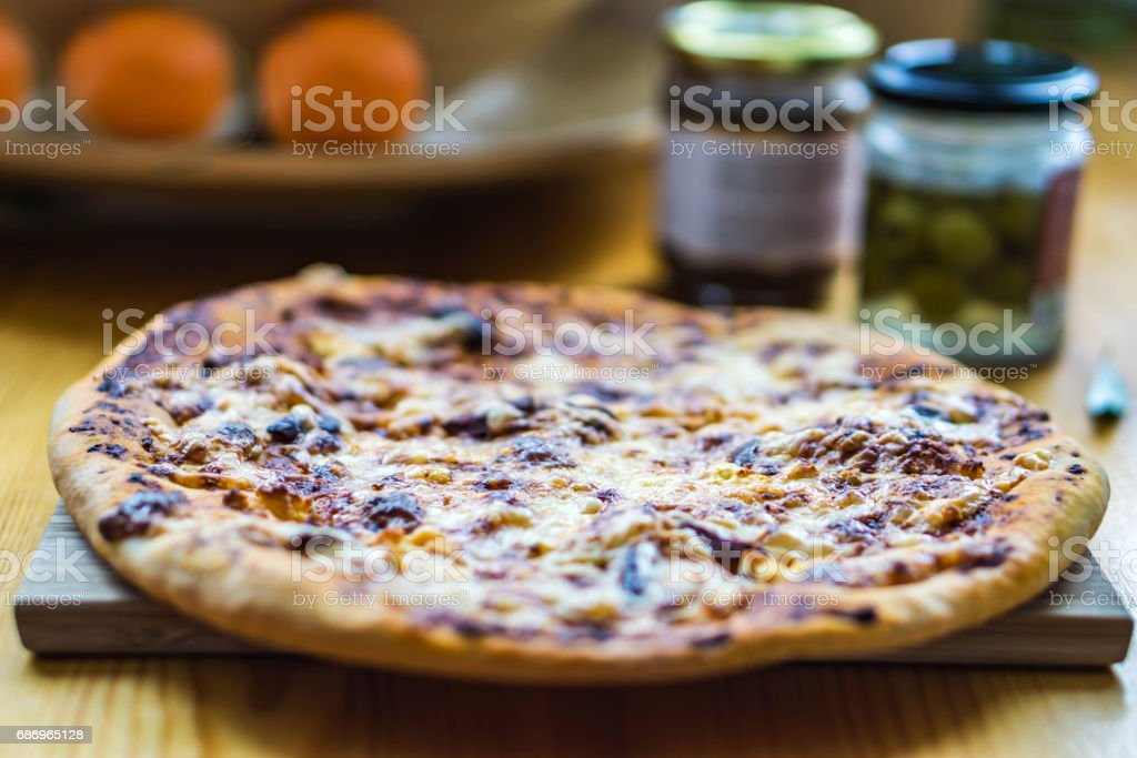 Homemade pizza with olives and sauce in the background stock photo