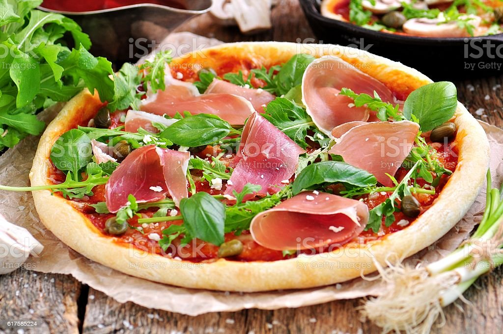 Homemade pizza with tomato sauce, mozzarella, organic arugula, Parma ham stock photo