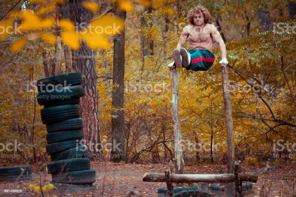 Homemade playground. Athlete swings abdominal muscles. stock photo