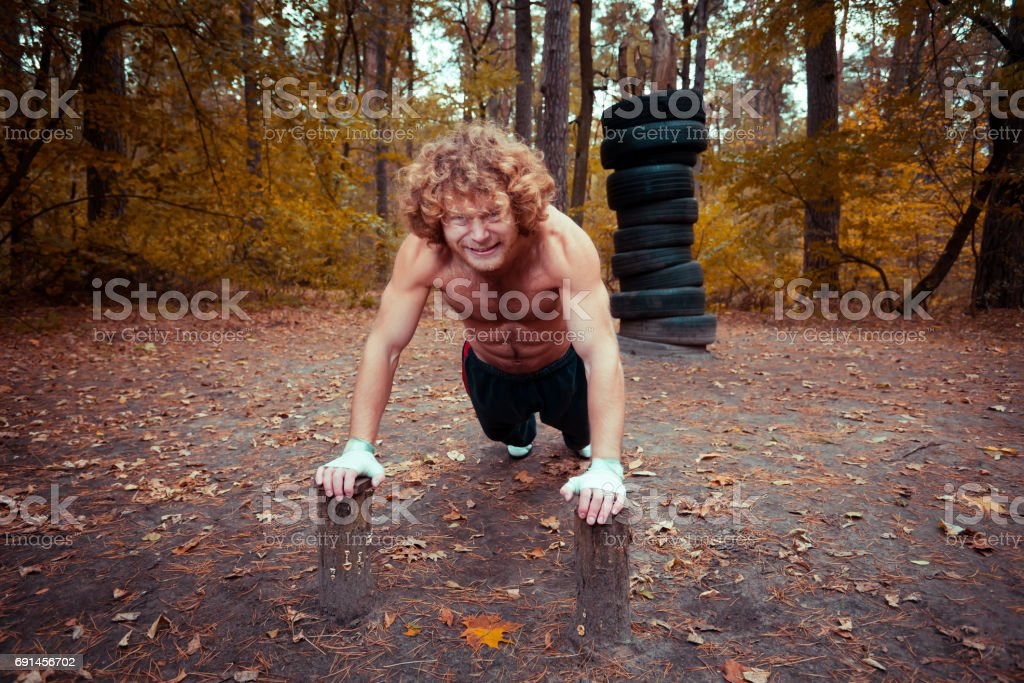 Homemade playground. Athlete swings the arm muscles. stock photo