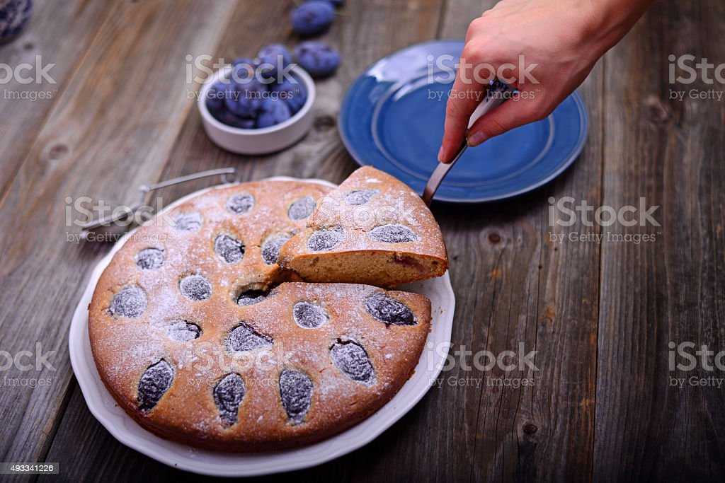 Homemade plum cake on wooden background stock photo