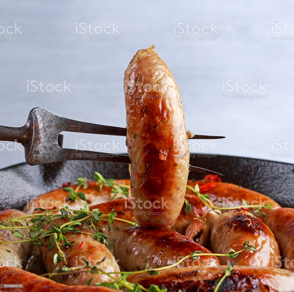 Home-made Pork Sausages in rustic pan with thyme stock photo