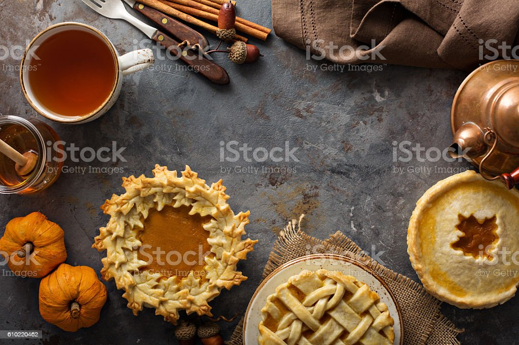 Homemade pumpkin pies decorated with fall leaves stock photo