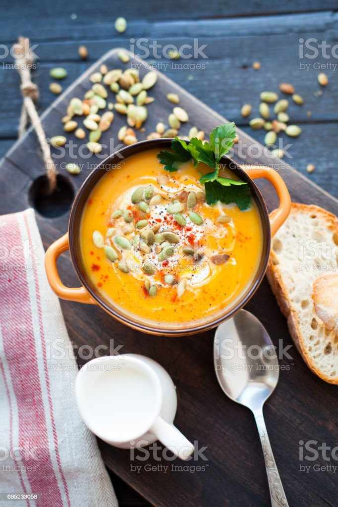 Homemade pumpkin soup with cream, bread, greens and pumpkin seeds on a wooden background. Top viev stock photo