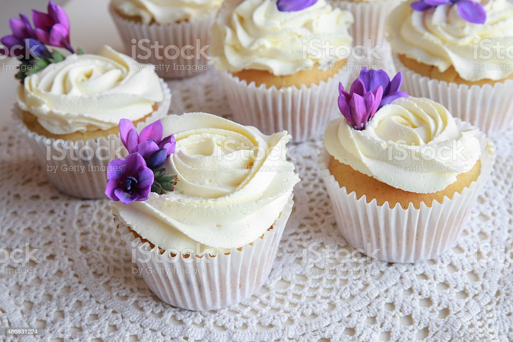 Homemade purple freesia flowers on vanilla cupcakes with whipped stock photo