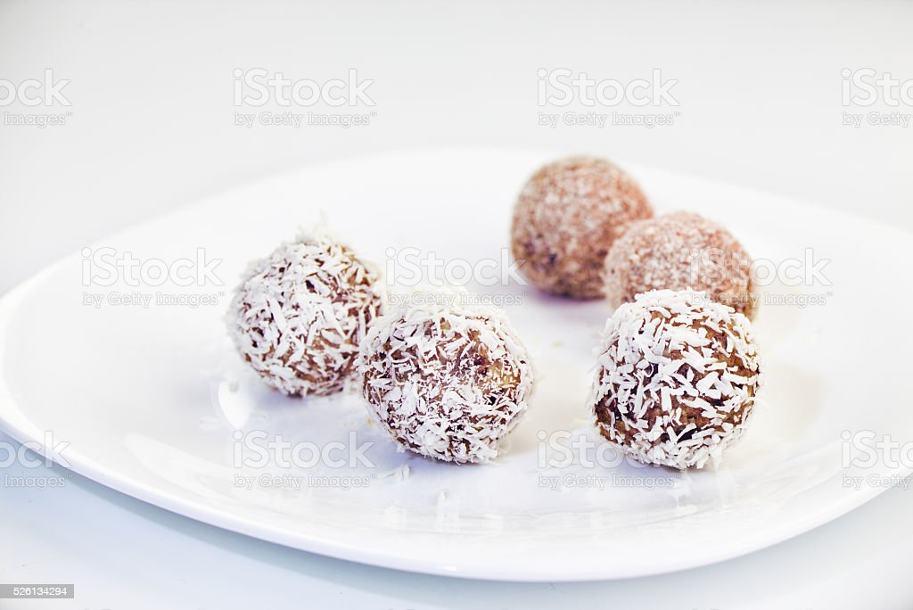 Homemade raw dates truffles with nuts, psyllium and coconut flakes stock photo