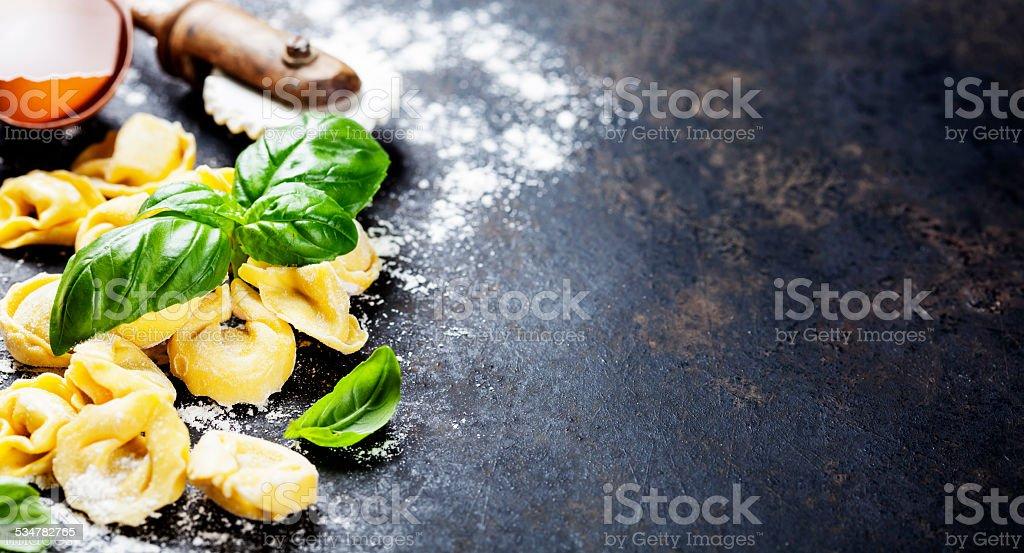 Homemade raw Italian tortellini and basil leaves stock photo