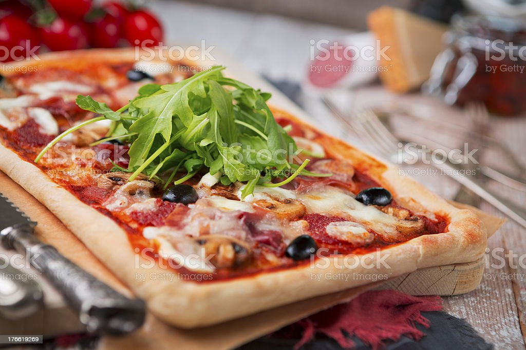 Homemade rectangular pizza on a rustic table with ingredients royalty-free stock photo