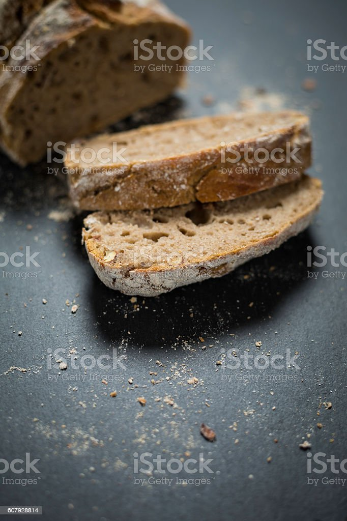 homemade rye bread with slices on black stone plate stock photo