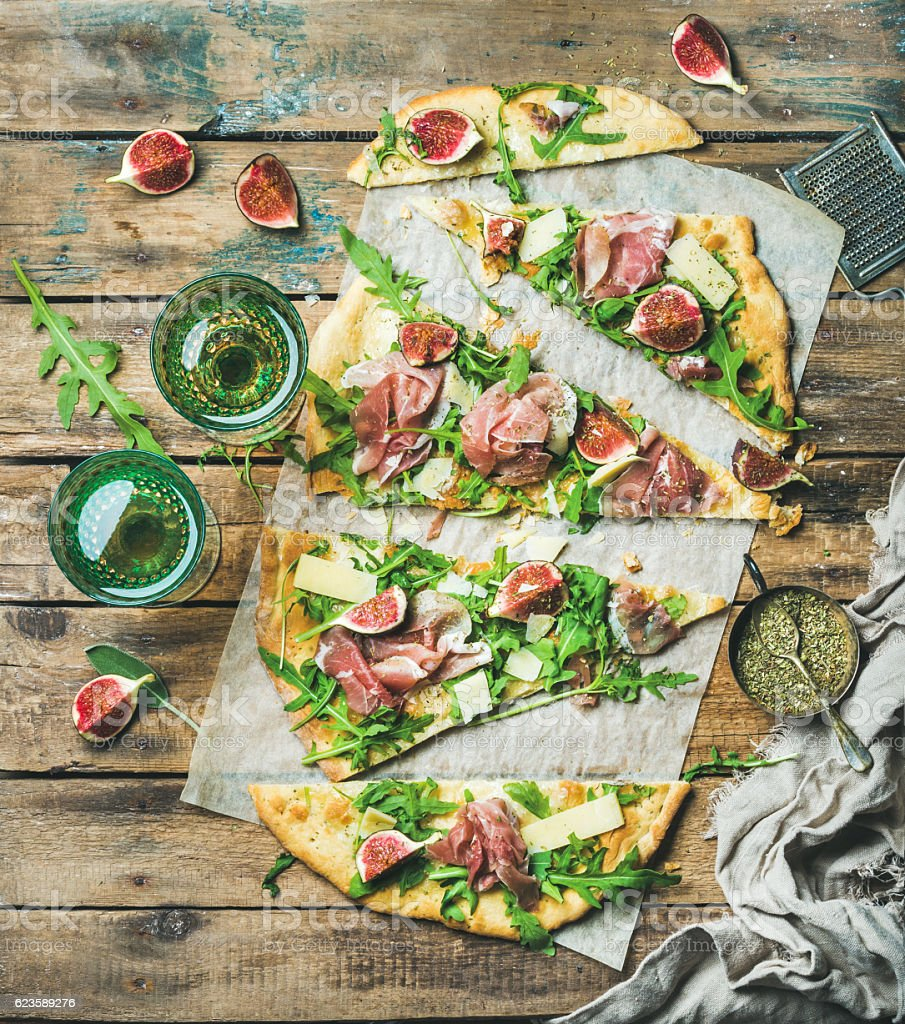 Homemade sage flatbread pizza cut into pieces with rose wine stock photo