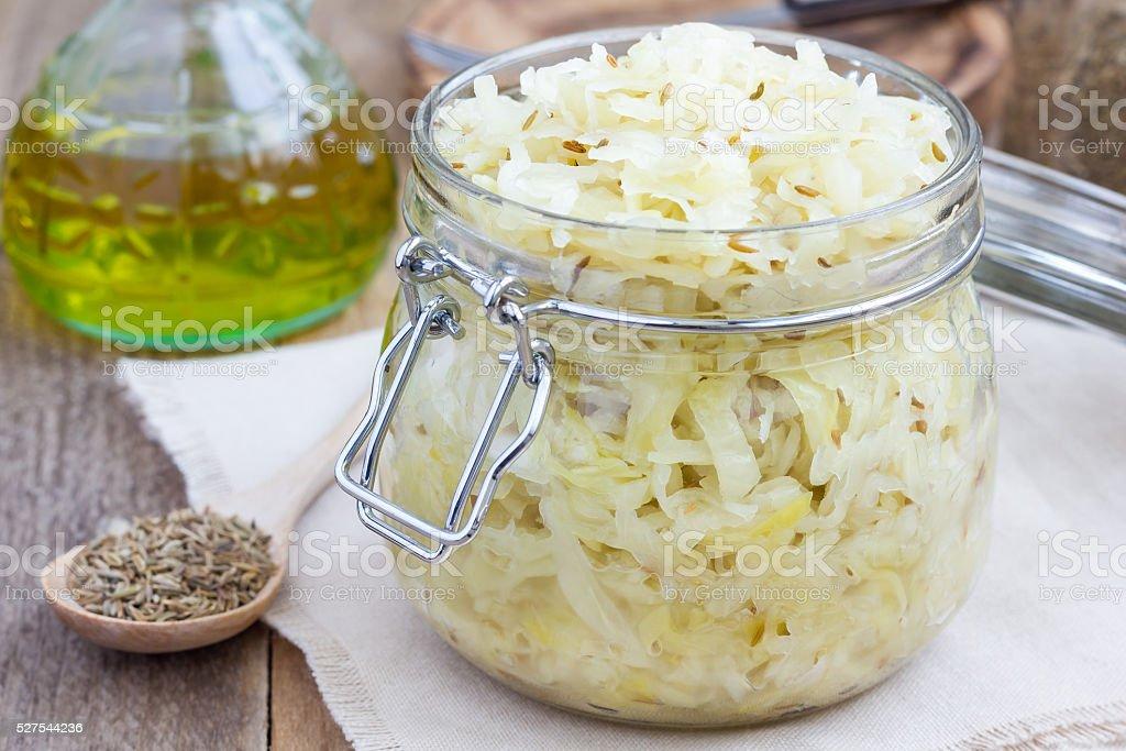 Homemade sauerkraut with cumin in a glass jar stock photo