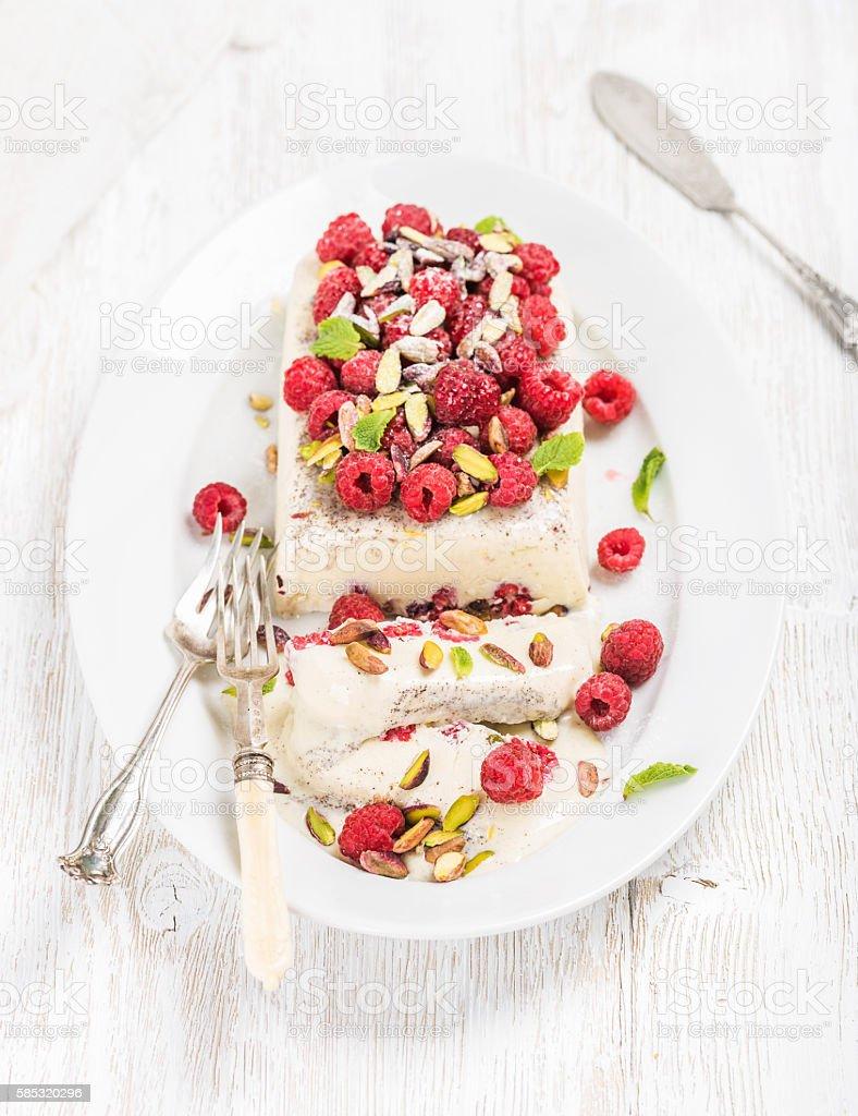 Homemade semifreddo with pistachio and fresh raspberries stock photo