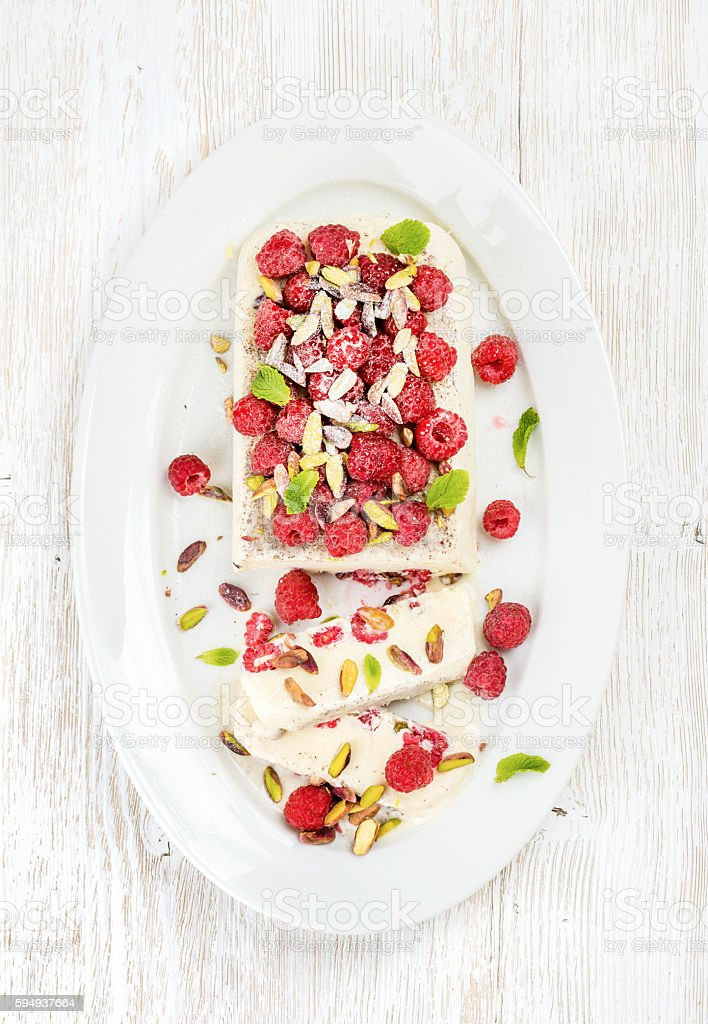 Homemade semifreddo with pistachio, raspberries and mint leaves stock photo