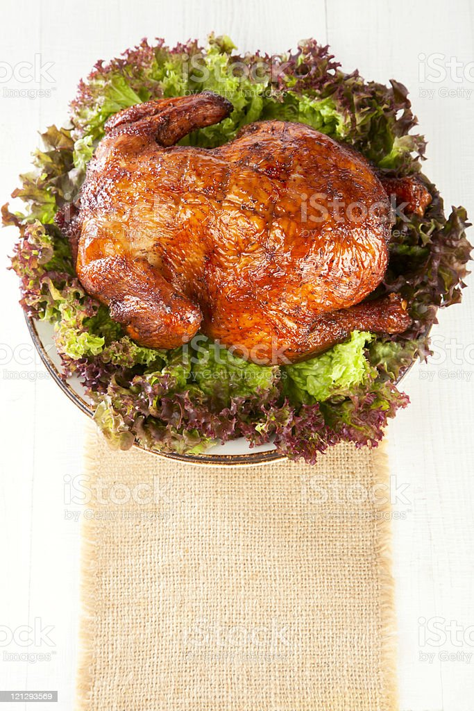 homemade smoked whole chicken on leaf lettuce bed and plates stock photo