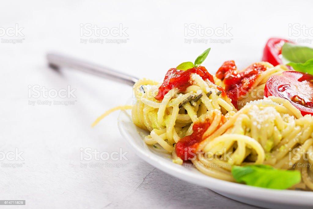 Homemade spaghetti pasta with avocado, tomato and basil sauce stock photo