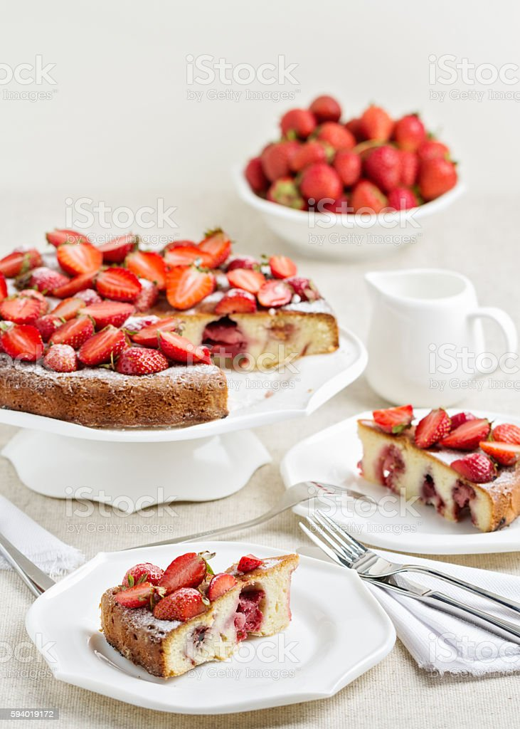 Homemade strawberry cake on a white cake stand. stock photo