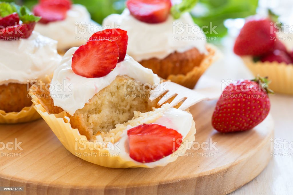 Homemade strawberry cupcakes with whipped cream stock photo