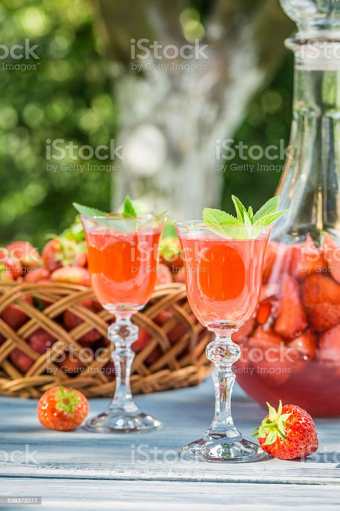 Homemade strawberry liqueur served in the garden stock photo