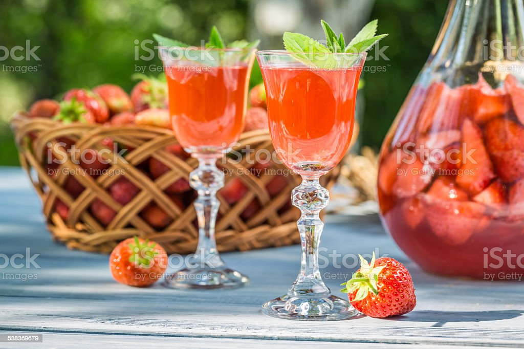 Homemade strawberry liqueur with mint stock photo