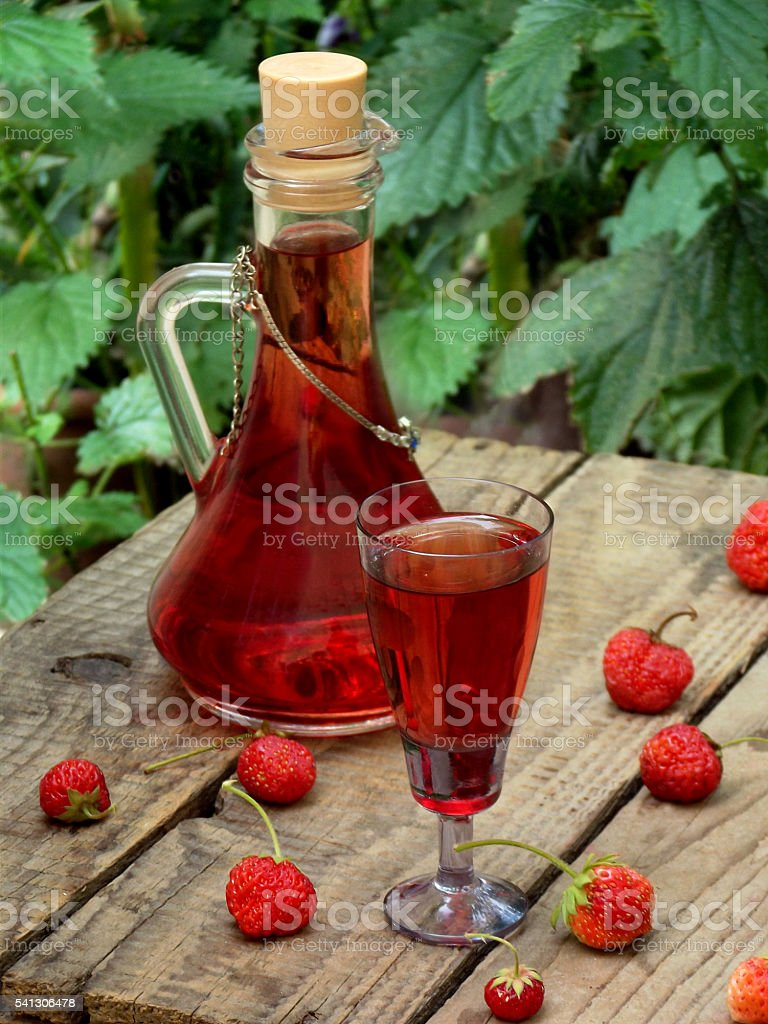 homemade strawberry liquor on a wooden background stock photo
