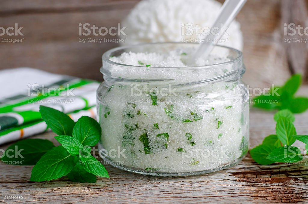 Homemade sugar scrub with mint leaves and essential mint oil stock photo
