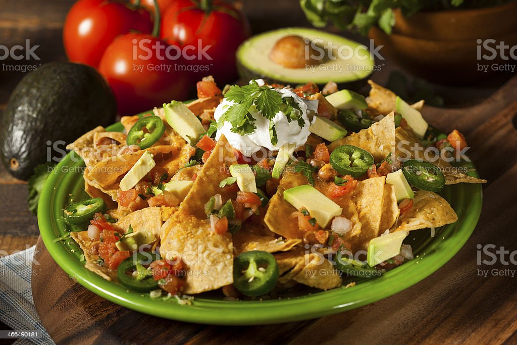 Homemade Unhealthy Nachos with Cheese and Vegetables stock photo