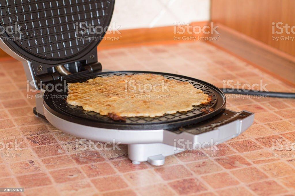 Homemade waffles in a waffle iron stock photo