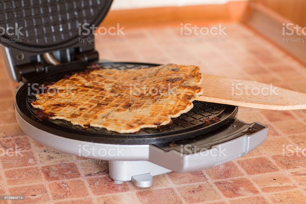 Homemade waffles in a waffle iron with wood spatula. stock photo