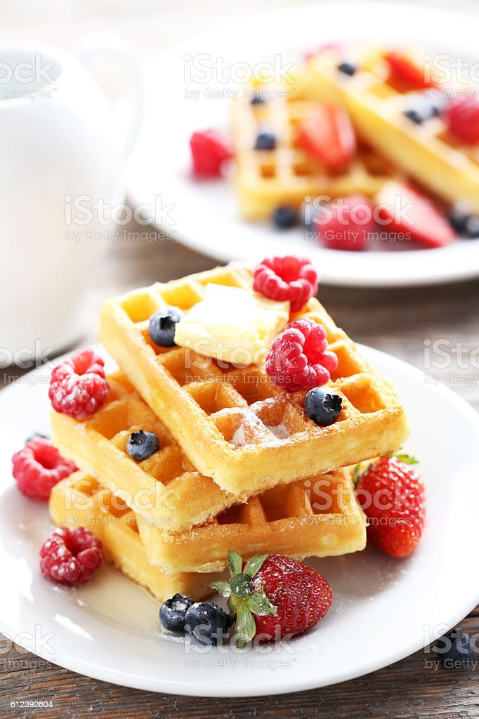 Homemade waffles with berries in plate on grey wooden table stock photo