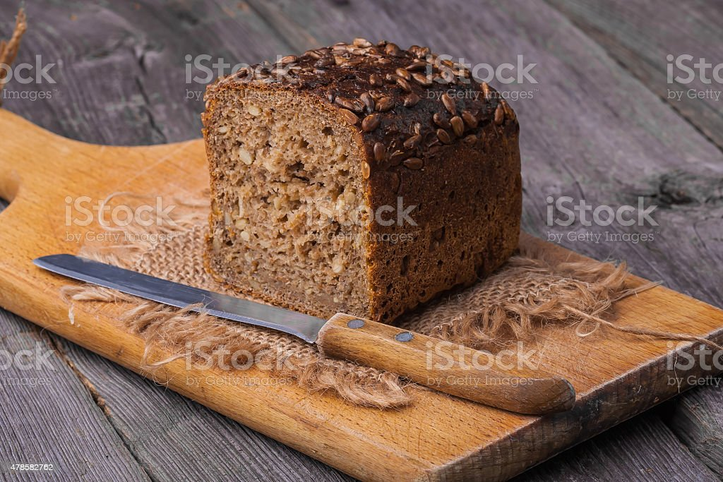 Homemade wholemeal bread on wooden table with knife stock photo