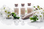 homeopathic pills with spring flowers on white wooden background