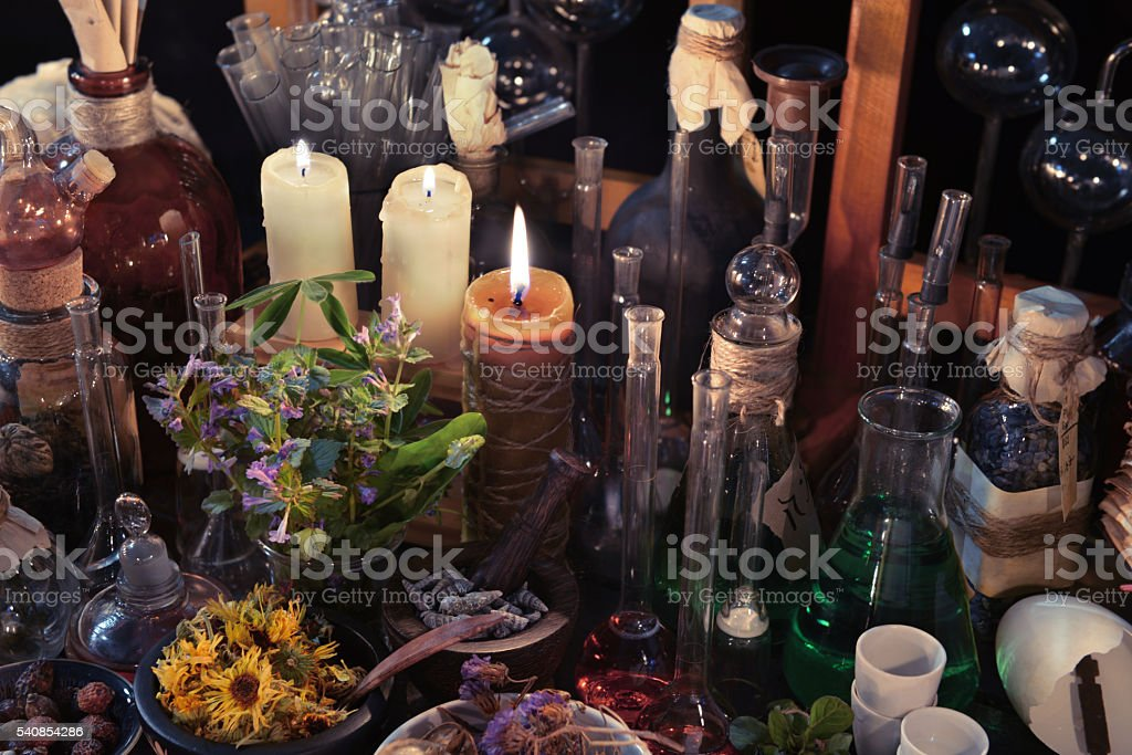 Homeopathic still life with bottles, flasks, old candle and herbs stock photo