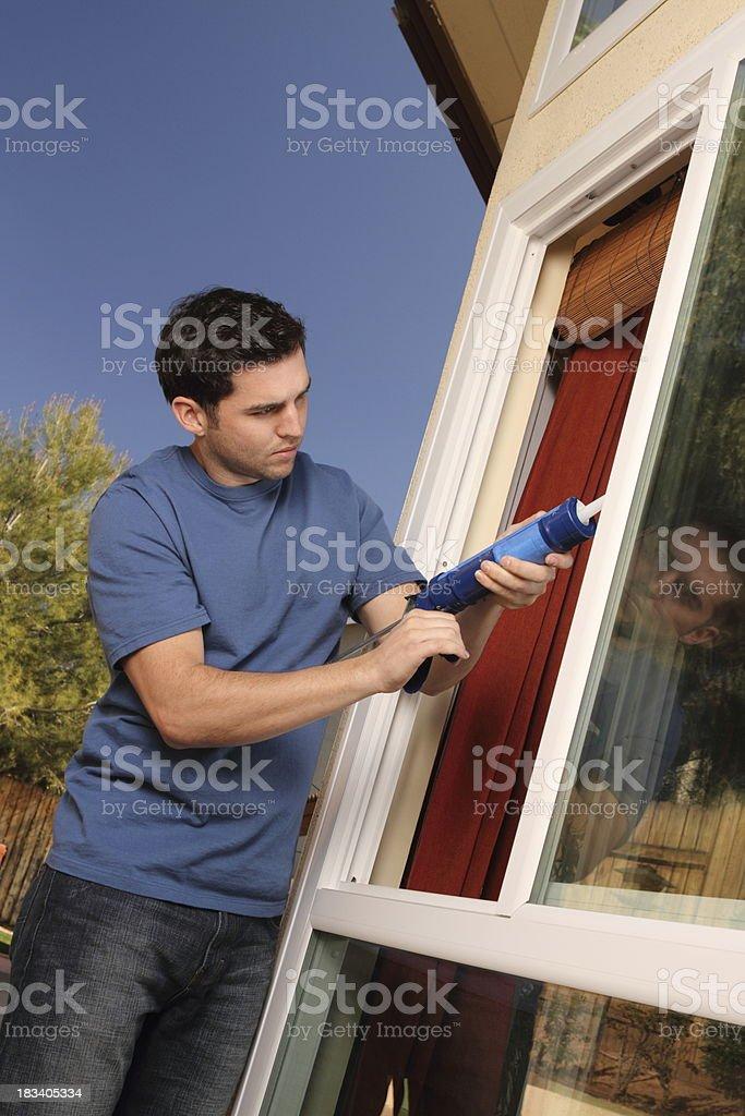 Homeowner Caulks Kitchen Window Angle stock photo