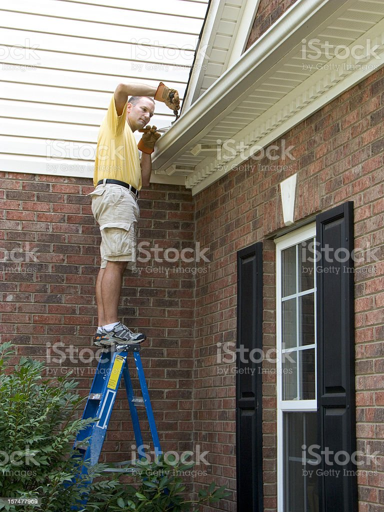 Homeowner Maintenance, Gutter Cleaning Working. Dangerously Standing On Ladder royalty-free stock photo