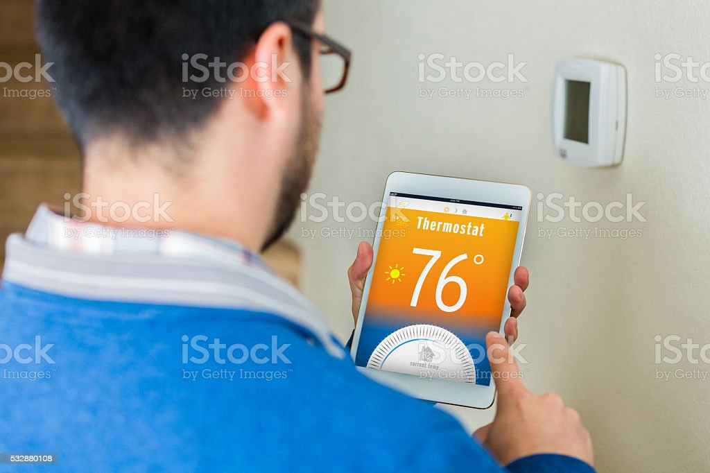 Homeowner uses digital table to control thermostat in his home stock photo