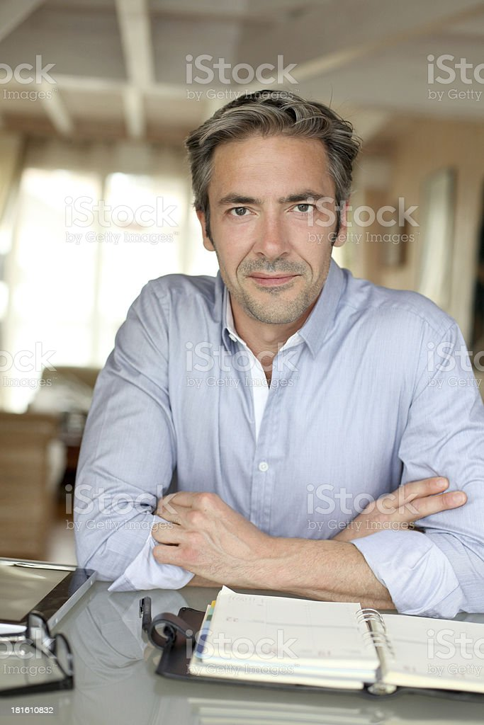 Homeworker with a serious look sitting on desk royalty-free stock photo