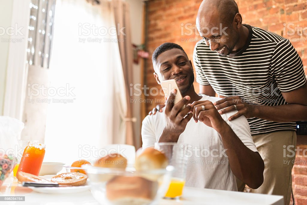 homosexual couple doing breakfast on the kitchen togetherness stock photo