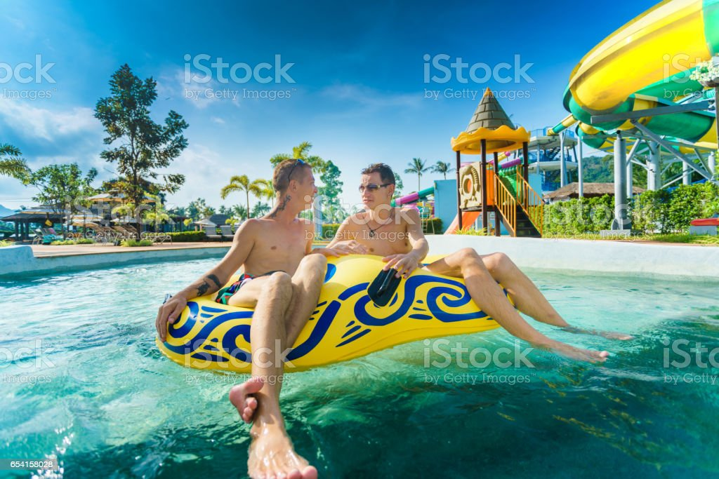 Homosexual couple having fun in waterpark stock photo
