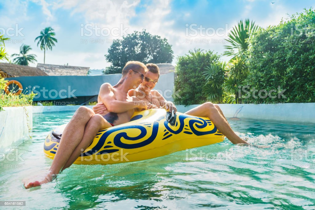 Homosexual couple having fun in waterpark stock photo