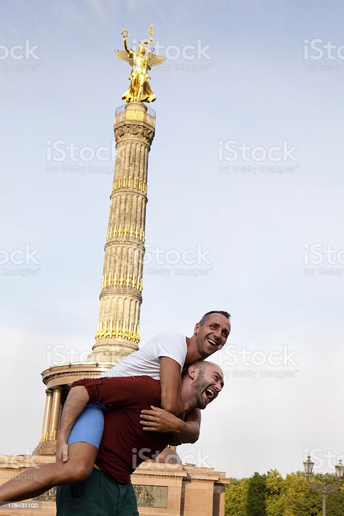 homosexual couple piggyback in front of Berlin Victory Column royalty-free stock photo