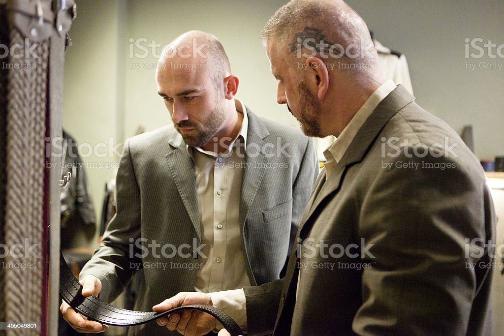 homosexual couple while looking for leather belts in a shop royalty-free stock photo