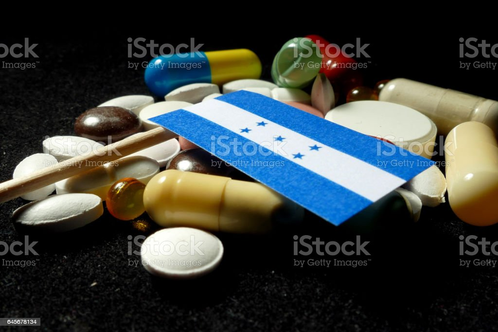 Honduran flag with lot of medical pills isolated stock photo