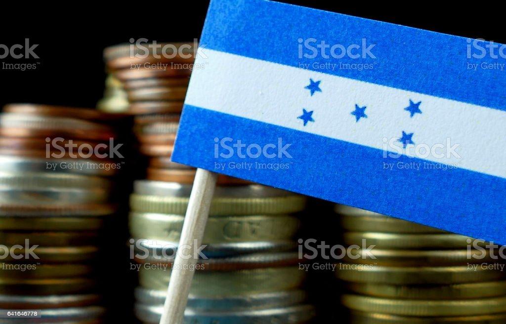 Honduras flag waving with stack of money coins macro stock photo