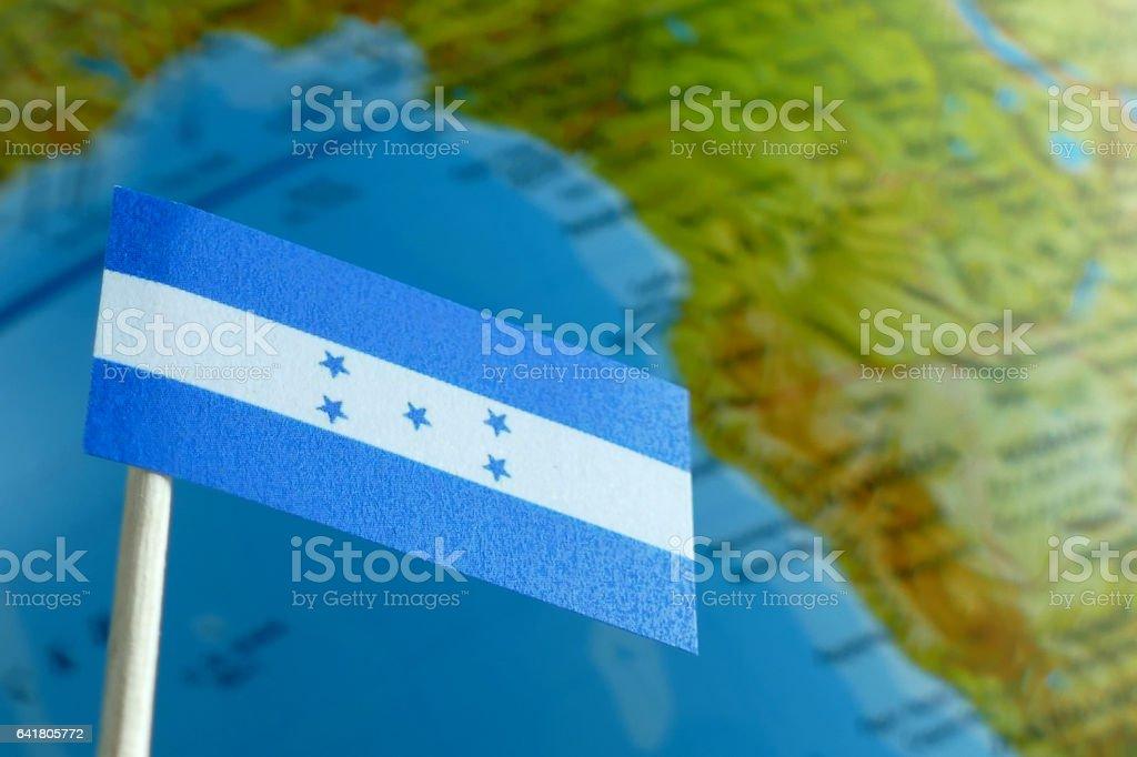 Honduras flag with a globe map as a background macro stock photo