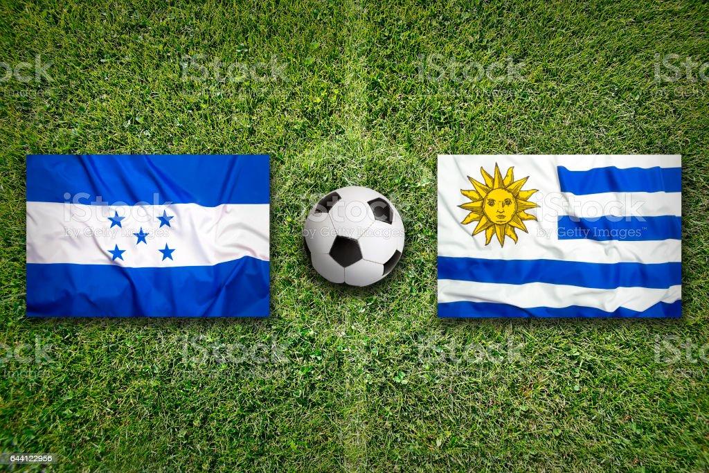 Honduras vs. Uruguay flags on soccer field stock photo