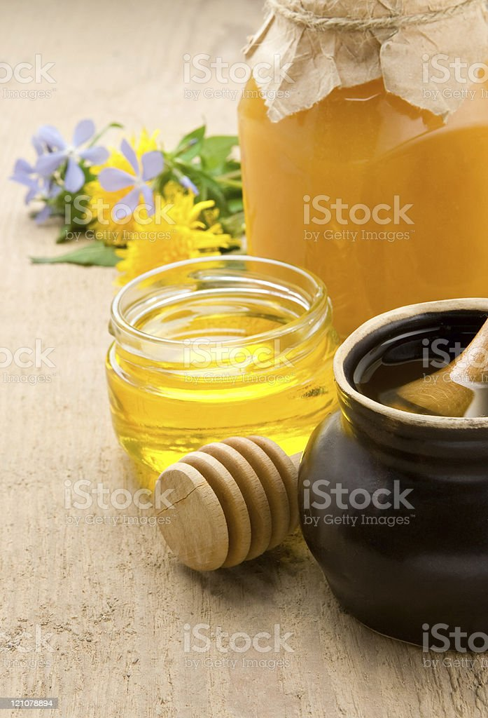 honey and flowers in glass jars on wood royalty-free stock photo