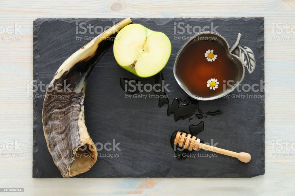 Honey, apple and horn on slate board. Rosh hashanah (jewish New Year holiday) concept stock photo