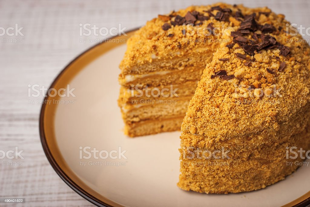 Honey cake  with chocolate chips and slice cut out stock photo