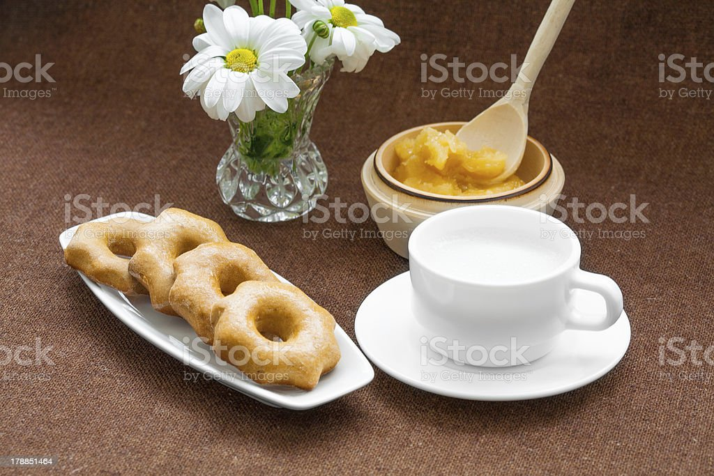 honey cookies, cup and a vase of daisies royalty-free stock photo